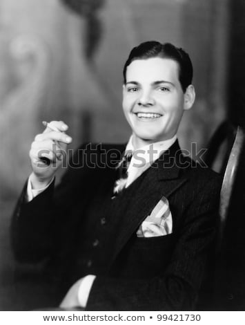 young smiling man with retro camera smoking cigarette stock photo © deandrobot