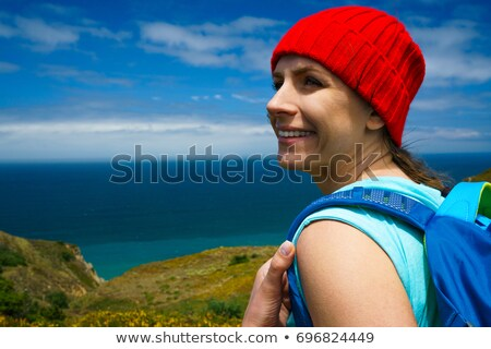 Woman with a backpack goes on a picturesque hilly terrain to the Stock photo © vlad_star