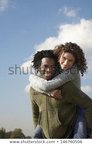 Woman enjoying piggyback ride Stock photo © deandrobot