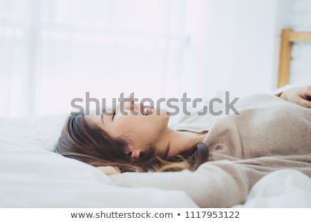 Foto stock: Smiling Asian Woman In Sweater Lying On A Couch
