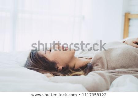 ストックフォト: Smiling Asian Woman In Sweater Lying On A Couch