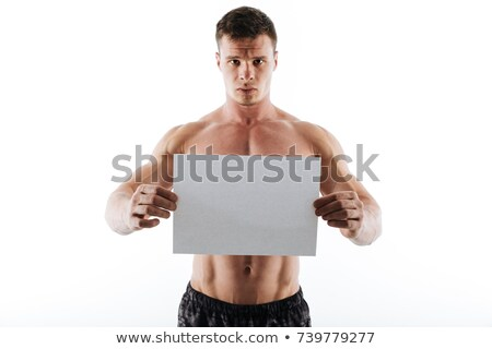 Serious handsome young sportsman holding copyspace paper Stock photo © deandrobot