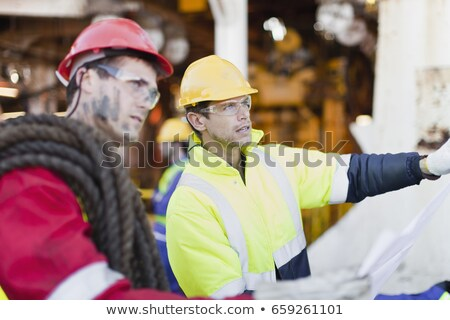 Workers examining blueprints on oil rig Stock photo © IS2