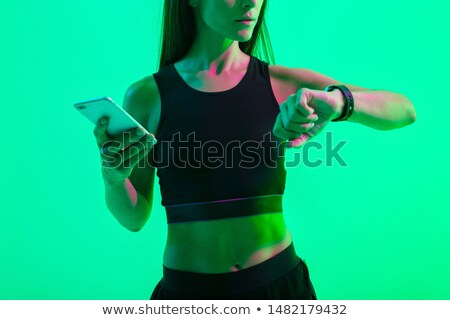 Cropped photo of strong young sports woman chatting by phone. Stock photo © deandrobot