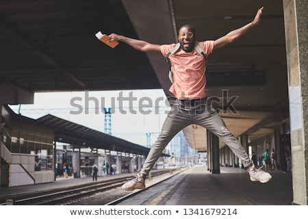 Full length portrait of a joyful excited man holding passport stock photo © deandrobot