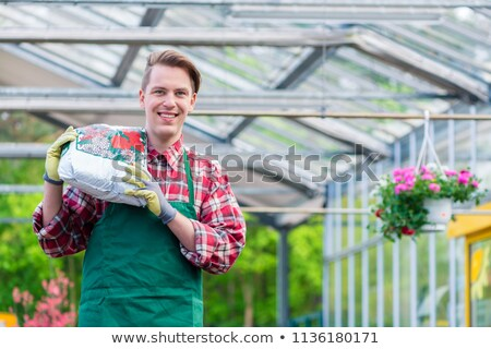 Cheerful young man carrying a bag of potting soil while working in a flower shop Stock photo © Kzenon