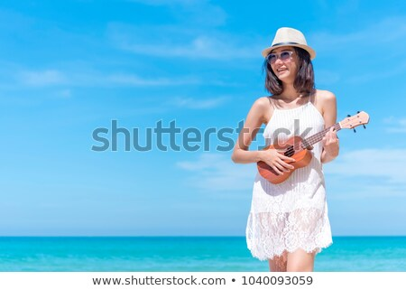 Stock photo: Pretty young woman with guitar on beach