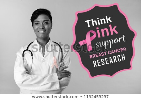 Smiling woman crossing arms for breast cancer awareness with pink ribbon  Stock photo © wavebreak_media