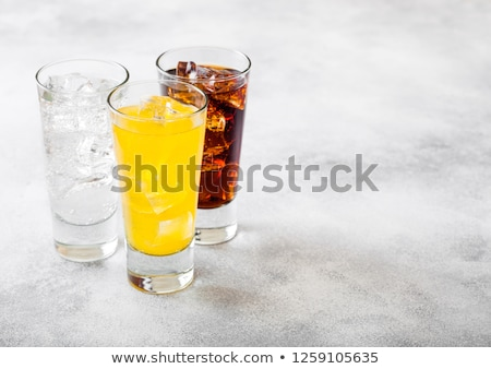 Glass of cola soda drink with ice cubes and bubbles on stone kitchen table background. Stock photo © DenisMArt