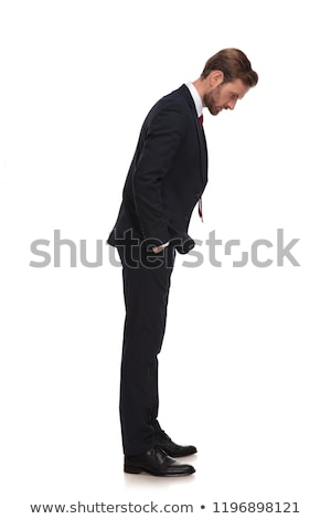 curious businessman in navy suit looks to side while standing Stock photo © feedough