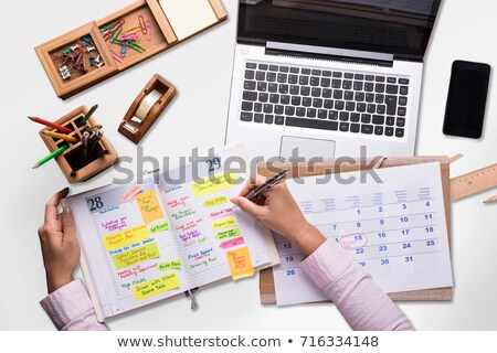 businesswoman holding cellphone writing schedule in diary stock photo © andreypopov