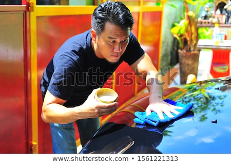 Man at work cleaning automobile at car wash waxy Stock photo © Lopolo