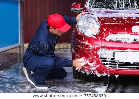 Man at work cleaning automobile at car wash Stock photo © Lopolo