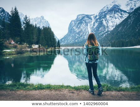 Young woman with backpack is standing on the coast of the lake  Stock photo © denbelitsky
