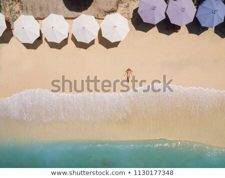 Jonge vrouw bikini ontspannen zandstrand zwarte zonnebril Stockfoto © AndreyPopov