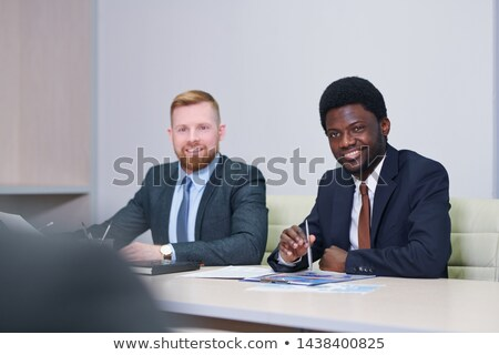Two intercultural businessmen in formalwear interacting with partner Stock photo © pressmaster