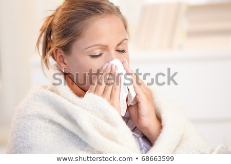 young woman having flu feeling bad blowing her nose stock photo © lopolo