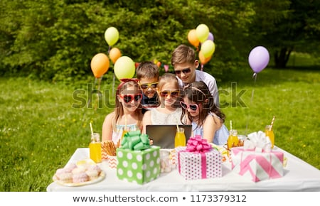 happy kids with tablet pc on birthday party Stock photo © dolgachov