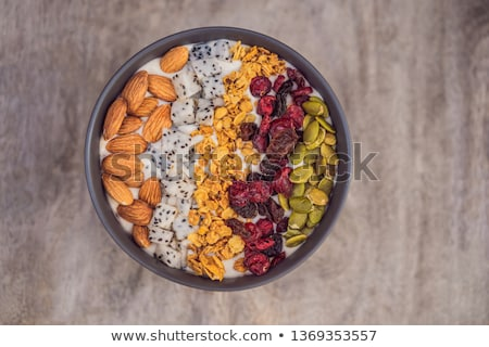 Mango smoothies bowl with almond, dragon fruit, dried cherries, pumpkin seeds and granola on wooden  Stock photo © galitskaya