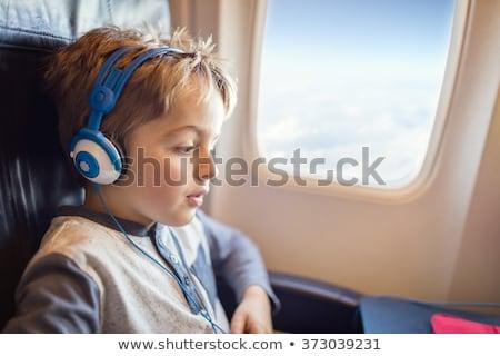 Menino fones de ouvido assistindo escuta vôo diversão Foto stock © galitskaya