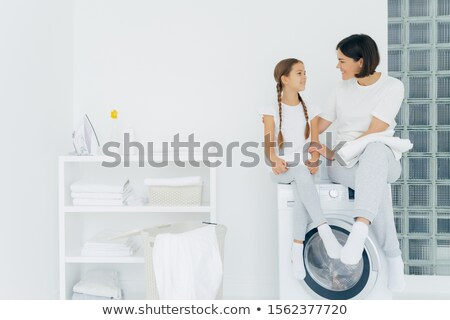 Caring mother talks with daughter, pose on washing machine, surrounded with white linen, do washing  Stock photo © vkstudio