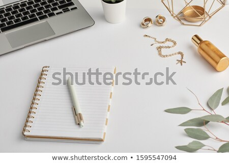 Gold earrings and chain, notebook with pen, bottle of scent and laptop keypad Stock photo © pressmaster