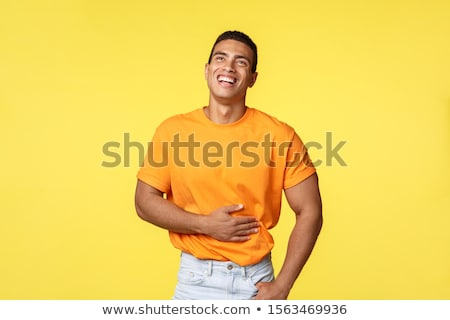 Man feeling pain abdominal muscles as laughing out loud from hilarious comedy or joke, chuckling, to Stock photo © benzoix