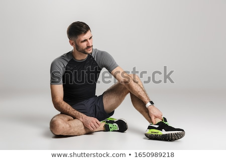 Image of unhappy sportsman with injury sitting while working out Stock photo © deandrobot