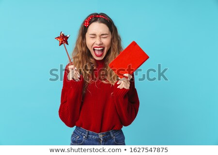 Image of delighted blonde woman holding notebook and magic wand Stock photo © deandrobot