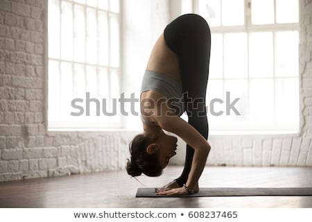 Woman Practicing Standing Forward Bend Yoga Exercise Stock photo © rognar
