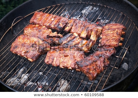 grilled pork ribs on bbq grill with a shallow dof stock photo © ruslanomega