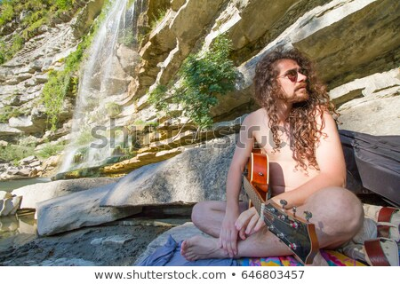 fashion man sitting and playing with his long beard stock photo © feedough