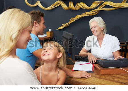 Foto stock: Hotel Receptionist Helping Family To Check In
