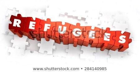 refugees   white word on red puzzles stock photo © tashatuvango