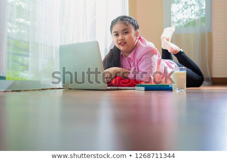 Beautiful woman lying on floor, hugging pillow and using laptop Stock photo © deandrobot