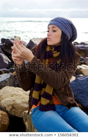 cheerful woman using photo camera and taking pictures in winter stock photo © deandrobot