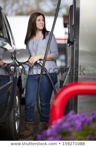 Woman fills petrol into her car Stock photo © vlad_star