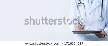 Female doctor in white uniform writing on clipboard paper Stock photo © stevanovicigor