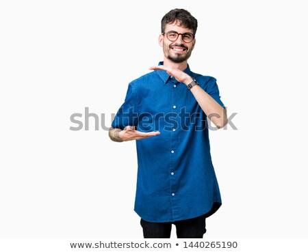 Hipszter mutat kezek kamera néz szürke Stock fotó © deandrobot