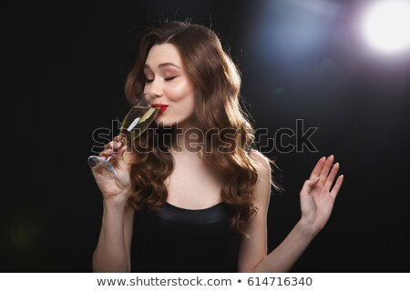 smiling pretty young woman standing and drinking chamagne stock photo © deandrobot