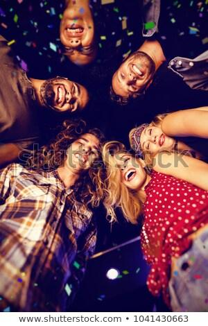 Directly below shot of happy friends standing in club Stock photo © wavebreak_media