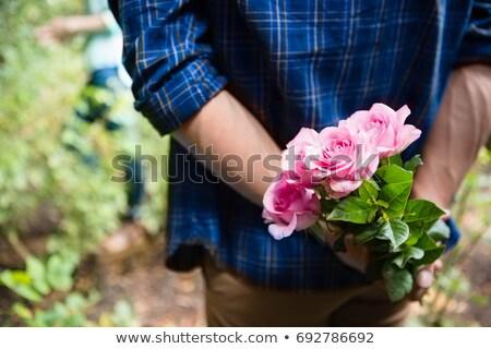 Homem ocultação flores atrás de volta jardim Foto stock © wavebreak_media