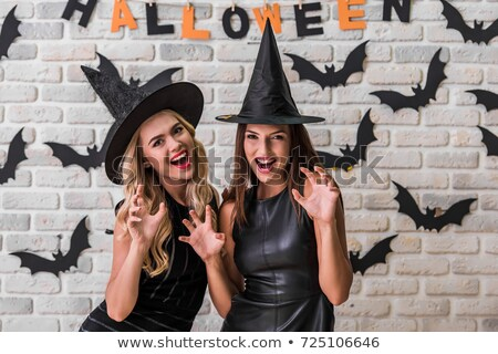 two happy young women in leather halloween costumes stock photo © deandrobot