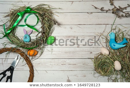 Stock photo: Easter wreath decoration. Branch of willow and colored eggs on blue wooden background