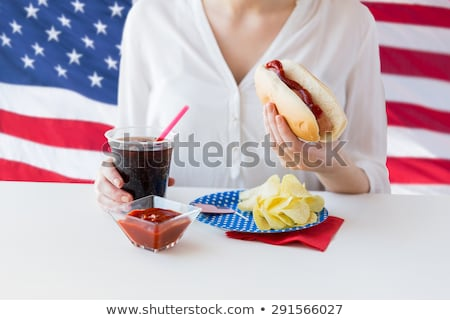 Stockfoto: Close Up Of Woman Eating Hot Dog With Cola