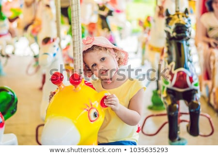Cute little boy and girl enjoying in funfair and riding on colorful carousel house Stock photo © galitskaya