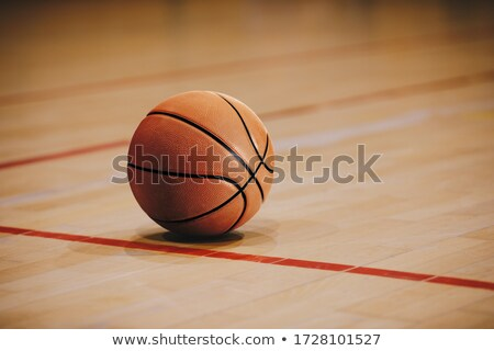 Basketball on Wooden Court Floor Close Up with Blurred Arena Stock photo © matimix