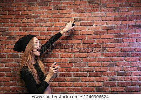 Image of beautiful hip hop woman 20s, drawing on brick wall with Stock photo © deandrobot