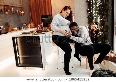 happy pregnant wife and husband at christmas tree stock photo © dolgachov