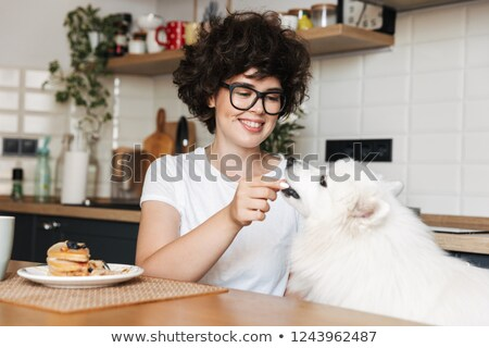 Pretty curly woman sitting at the kitchen eat cake and feed her cutie white dog. Stock photo © deandrobot